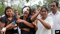 Anusha Kumari, center, weeps during a mass burial for her husband, two children and three siblings, all victims of Easter Sunday's bomb attacks, in Negombo, Sri Lanka, April 24, 2019.