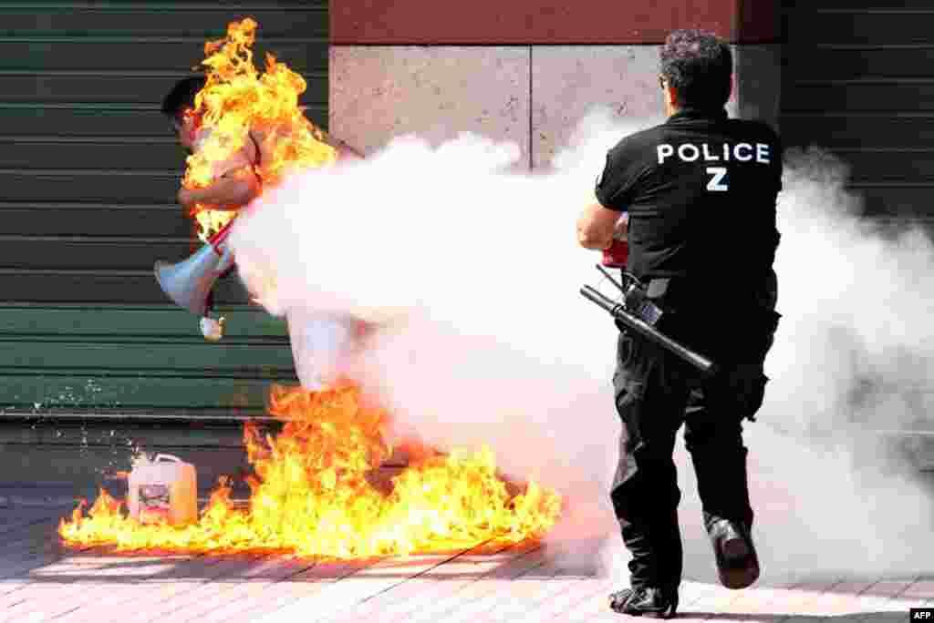 16 tháng 9: Cảnh sát Hy Lạp chữa cháy cho một doanh nhân tự thiêu trước ngân hàng Piraeus. Doanh nhân cho biết ông bị sạt nghiệp sau khi vay nhiều khoản nợ của ngân hàng này. (AP Photo/Nontas Stlianidis)