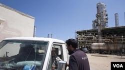 Pekerja Libya berbicara di dekat fasilitas penyulingan minyak Zawiya, dekat Tripoli. Uni Eropa akan menghapuskan sanksi minyak atas Libya, sehingga perusahaan minyak Libya akan bisa kembali beroperasi.