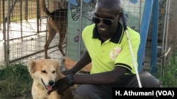 Francis Okello Oloya, founder of The Comfort Dog Project, interacts with Binongo in Gulu, Uganda.