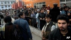 人们聚集在救治塔利班袭击中受伤学生们的医院前