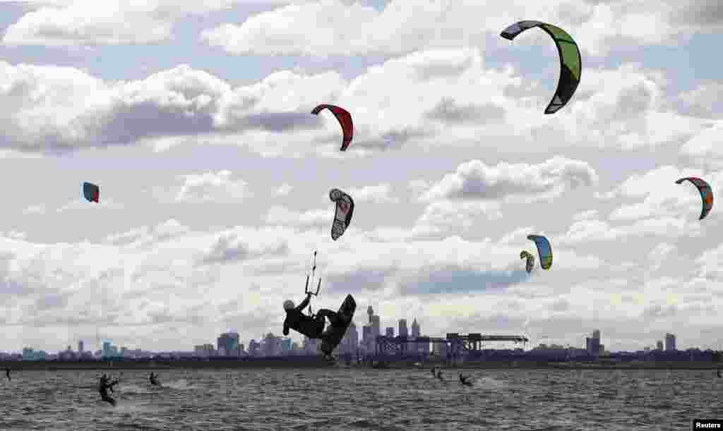 Kite surfers take advantage of strong westerly winds and choppy waves on Sydney's Botany Bay, Australia.