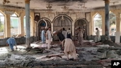 People view the damage inside of a mosque following a bombing in the provincial capital of Kunduz, northern Afghanistan, Oct. 8, 2021.