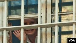 Mantan PM Ukraina, Yulia Tymoshenko melambai kepada para pendukungnya dari jendela penjara di Kyiv (4/11).