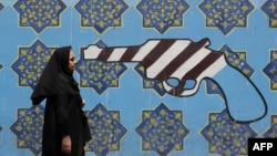 An Iranian woman walks past a mural depicting a gun painted on the wall of the former US embassy in the capital Tehran.