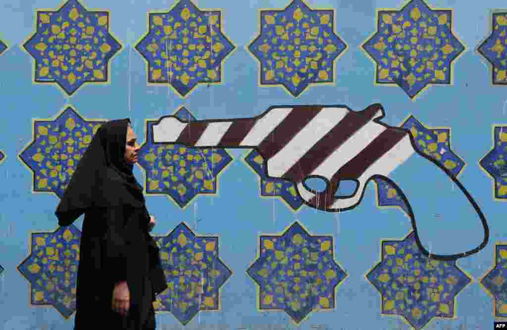 An Iranian woman walks past a mural depicting a gun painted on the wall of the former U.S. embassy in the capital Tehran.
