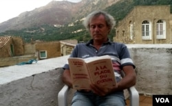 A French man reads Arnaud Cathrine's latest novel, set during the January 2015 terrorist attacks. (L. Bryant/VOA)