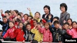 지난달 북한 접경 도시 신의주에서 압록강변으로 소풍나온 어린이들이 중국 쪽을 향해 손을 흔들고 있다.