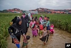 Rohingya Muslims, who crossed over from Myanmar into Bangladesh, wade past a waterlogged path leading to the Jamtoli refugee camp in Ukhiya, Bangladesh, Nov. 17, 2017.