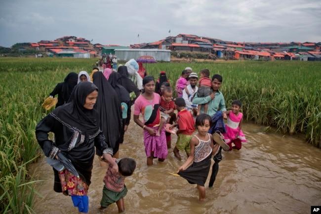 Rohingya Muslims, who crossed over from Myanmar into Bangladesh, wade past a waterlogged path leading to the Jamtoli refugee camp in Ukhiya, Bangladesh, Nov. 17, 2017.
