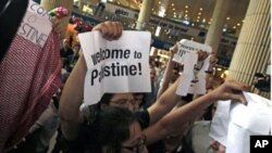 "Pro-Palestinian Israeli activists hold signs during a small demonstration at the arrival terminal at Ben Gurion International Airport near Tel Aviv in support of a ""fly-in"" by other pro-Palestinian activists to Tel Aviv over the weekend, July 8, 2011"
