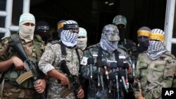 FILE - Masked Palestinian militants from Al Aqsa Martyrs' Brigade, a militia linked to the Fatah movement, give a press conference to condemn the decision by U.S. President Donald Trump to recognize Jerusalem as Israel's capital, in Gaza City, Dec. 7, 2017.