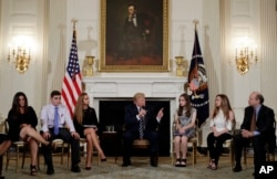 FILE - President Donald Trump speaks as he hosts a listening session with high school students, teachers and parents in the State Dining Room of the White House in Washington, Feb. 21, 2018.