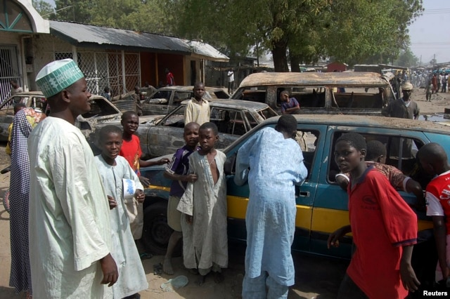 Residents survey vehicles damaged after a bomb blast at a primary school in Maiduguri, the capital of Nigeria's Borno state, February 29, 2012.