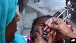 Seorang petugas kesehatan Pakistan memberi seorang anak vaksin polio di Lahore (5/5). (AP/K.M. Chaudary)
