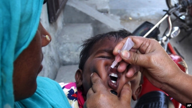 A Pakistani health worker gives a child a polio vaccine in Lahore, Pakistan, Monday, May 5, 2014.