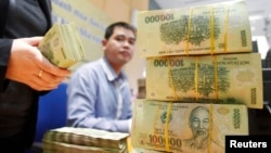 FILE - Stacks of 100,000 Vietnamese Dong notes ($4.70) are pictured as employees count money at a branch of the Bank for Investment and Development of Vietnam (BIDV) in Hanoi.