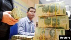 FILE - Stacks of 100,000 Vietnamese Dong notes are pictured as employees count money at a branch of the Bank for Investment and Development of Vietnam (BIDV) in Hanoi.