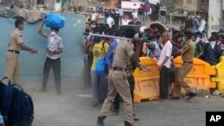 Polisi India berusaha mengatur para pekerja migran yang berusaha kembali ke rumah mereka di stasiun kota Mumbai, India (15/5).
