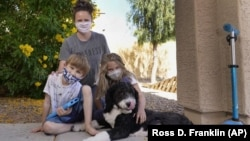 Christie Black, middle, with her two children, Angela and Luke, left, and the family dog Teddy, pose at their home, Tuesday, May 11, 2021, in Mesa, Ariz. (AP Photo/Ross D. Franklin)