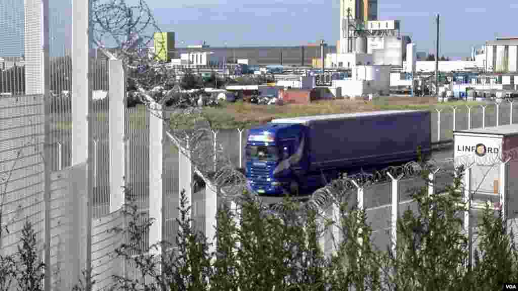 One of many fences erected around Calais to prevent migrants from boarding trucks, trains and ferries bound for Britain, is seen in Calais, France. (L. Bryant/VOA)