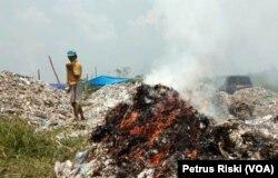 Proses pembakaran sampah plastik sisa pemilahan yang tidak laku dijual. (Foto: Petrus Riski/VOA)