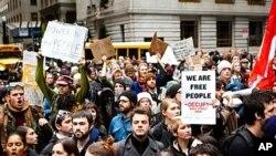 '佔領華爾街'示威者在紐約曼哈頓舉行大規模集會﹐在警方搭建的障礙物中尋找進入華爾街的通道。