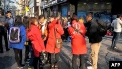 Turis asing bertanya kepada pemandu wisata Korsel berjaket merah, di sebuah jalan di ibukota Seoul, Selasa (9/4).