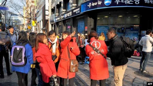 Foreign tourists consult with South Korean tour guides wearing red jackets in a crowded shopping district in Seoul on Apr. 9, 2013.
