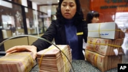 A local commercial bank staff receives bricks of dong bank notes from a customer in Hanoi, February 23, 2011