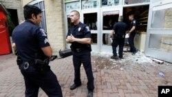 Cảnh sát đứng ngoài một cửa hàng bị phá hủy bắt nguồn từ những cuộc biểu tình suốt đêm sau vụ cảnh sát bắn chết ông Keith Lamont Scott hôm thứ Ba ở Charlotte, North Carolina, ngày 22 tháng 9 năm 2016.
