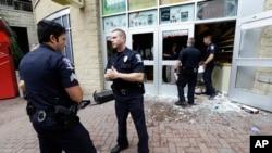 2016年9月22日,美国北卡夏洛特市,警察站在一个被抗议人群砸毁的店铺前面。