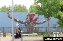 Women walk by graffiti in Grigny, which boasts 89 different nationalities.