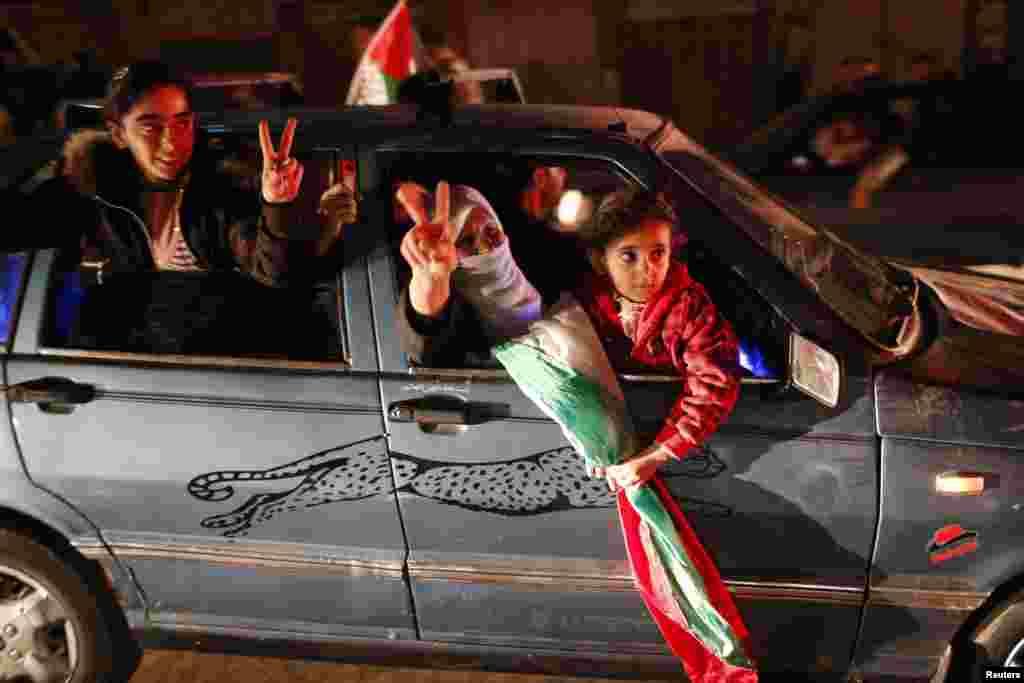 Palestinians celebrate on a street in Gaza City, November 30.