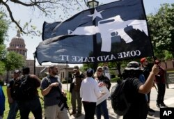"""A man holds a """"Come and Take It"""" flag during a pro gun-rights rally at the Capitol, April 14, 2018, in Austin, Texas. Gun rights supporters rallied across the United States to counter a recent wave of student-led protests against gun violence."""