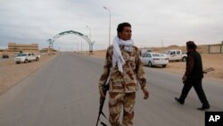 Pro-Gadhafi militiamen guard a checkpoint in Bin Jawad March 12, 2011