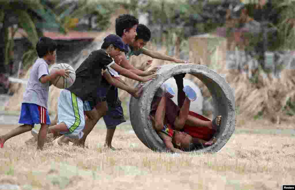 Filipinler'de drenaj borusu ile oyun oynayan çocuklar.