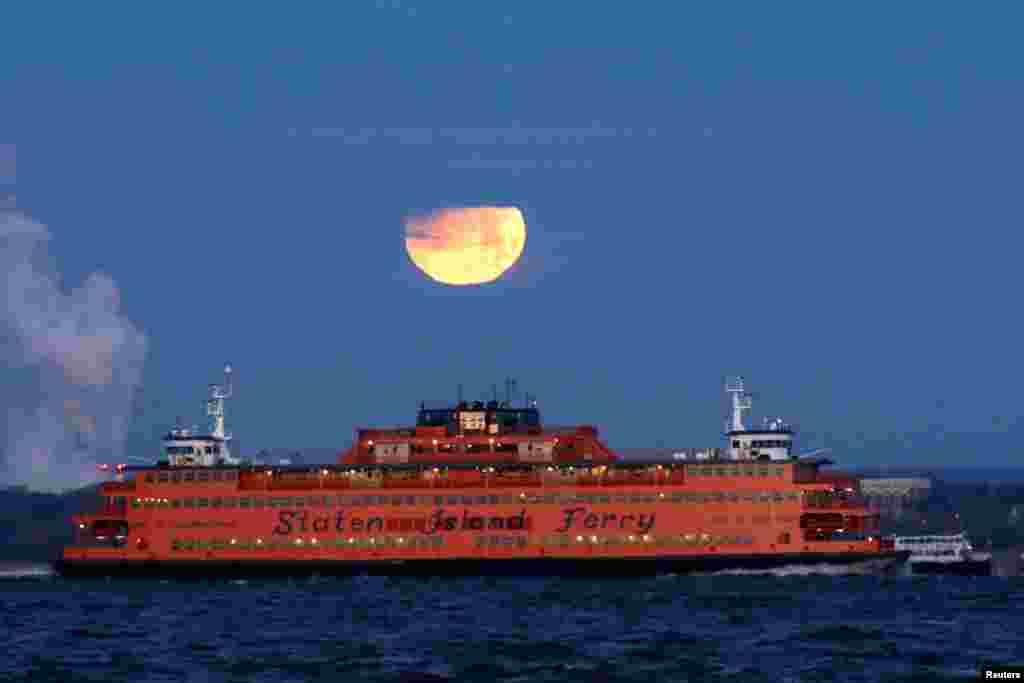 ព្រះចន្ទពេញវង់ក្រហម ឬ«The Super Blue Blood Moon» លិចនៅខាងក្រោយនាវា Staten Island Ferry ដែលអាចមើលឃើញពីទីក្រុង Brooklyn បុរីញូវយ៉ក។