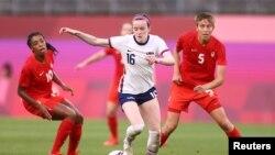 Pertandingan semi final sepak bola putri Tim AS melawan Kanada di stadion Ibaraki Kashima, Jepang, 2 Agustus 2021. Rose Lavelle (AS) diapit Ashley Lawrence (kiri) dan Quinn (kanan). (REUTERS/Edgar Su)