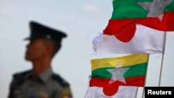 A police officer stands on guard near national flags of Myanmar and Japan during the commencement ceremony of the Thilawa Special Economic Zone (SEZ) project in the Japanese Special Economic Zone at Thilawa outside Yangon November 30, 2013. The first pha