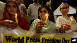 FILE - Pakistani journalists attend a candlelight vigil to observe the World Press Freedom Day, which was declared by the UN General Assembly in 1993, May 3, 2019, in Karachi, Pakistan.