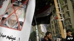 Người biểu tình Ai Cập đứng cạnh một tấm áp phích chống Thống chế Hussein Tantawi, người đứng đầu quân sự đương quyền tại Quảng trường Tahrir, ngày 27/11/2011