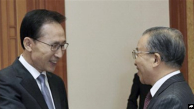 South Korean President Lee Myung-bak, left, shakes hand with Chinese State Councilor Dai Bingguo during their meeting at the presidential house in Seoul, South Korea, 28 Nov 2010.