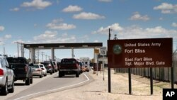 FILE - This Sept. 9, 2014, file photo shows cars waiting to enter Fort Bliss in El Paso, Texas. Fort Bliss is one of the two bases in Texas that the Trump administration has chosen to house thousands of detained migrants.