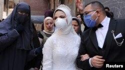Pasangan pengantin baru melakukan pernikahan di Kairo, Mesir di tengah perebakan Covid-19 di sana (foto: ilustrasi).