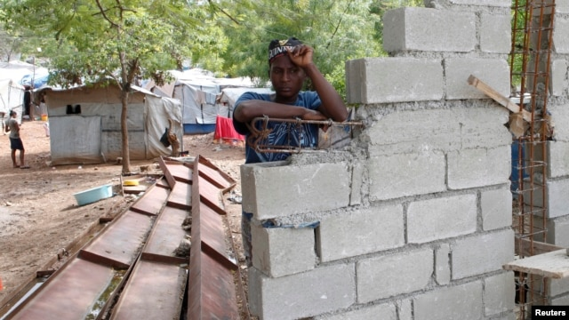 Haitian woman Romaine, one of the thousands made homeless by the 2010 earthquake, leans on a wall being built by the owners of the land where she lives in Shelter Camp 3, one of 385 informal 'tent cities' still existing since the disaster, in the Delmas suburb of Port-au-Prince, April 22, 2013.