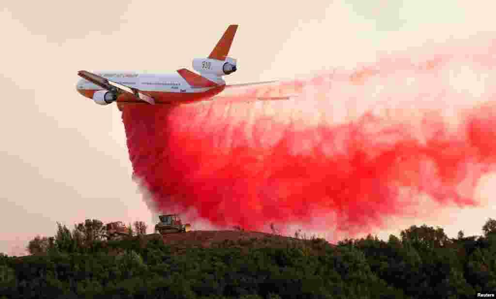 យន្តហោះ DC-10 ដឹកឧស្ម័ន បានបញ្ចេញសារធាតុទប់ស្កាត់ភ្លើងនៅតាមជើងភ្នំដើម្បីការពារគ្រឿងចក្រឈូសដីពីរគ្រឿងដែលកំពុងឈូសដីដើម្បីកាត់កុំឲ្យភ្លើងបន្តរាលដាល នៅតំបន់River Fire ជិតក្រុងLakeport រដ្ឋកាលីហ្វ័រញ៉ា។