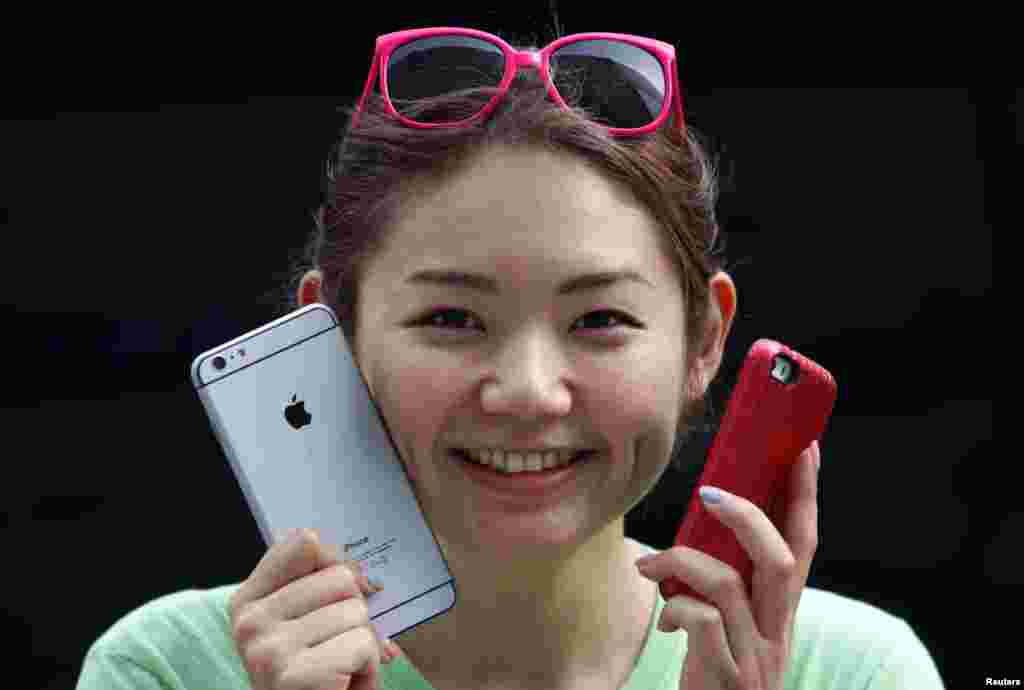 Một phụ nữ cầm một chiếc điện thoại iPhone 6 Plus giả (trái) và một chiếc điện thoại iPhone 5s trong khi đứng xếp hàng chờ iPhone 6 và iPhone 6 Plus được đem ra bán, phía trước một cửa hàng Apple tại khu mua sắm Ginza ở Tokyo, Nhật Bản, ngày 19 tháng 9, 2014.