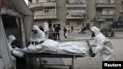 Kelompok medis dari Tentara Pembebasan Suriah melatih orang-orang mengatasi serangan senjata kimia di Aleppo, Desember 2013.