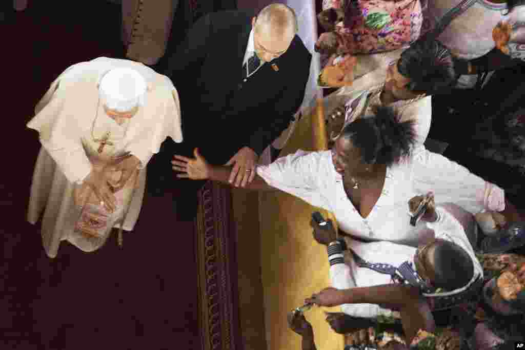 A body guard (C) for Pope Benedict XVI deflects the hand of a woman reaching towards the pontiff as he leaves the Basilica in the city of Ouidah in Benin, November 19, 2011. Pope Benedict said on Saturday the developed world could not continue to look dow